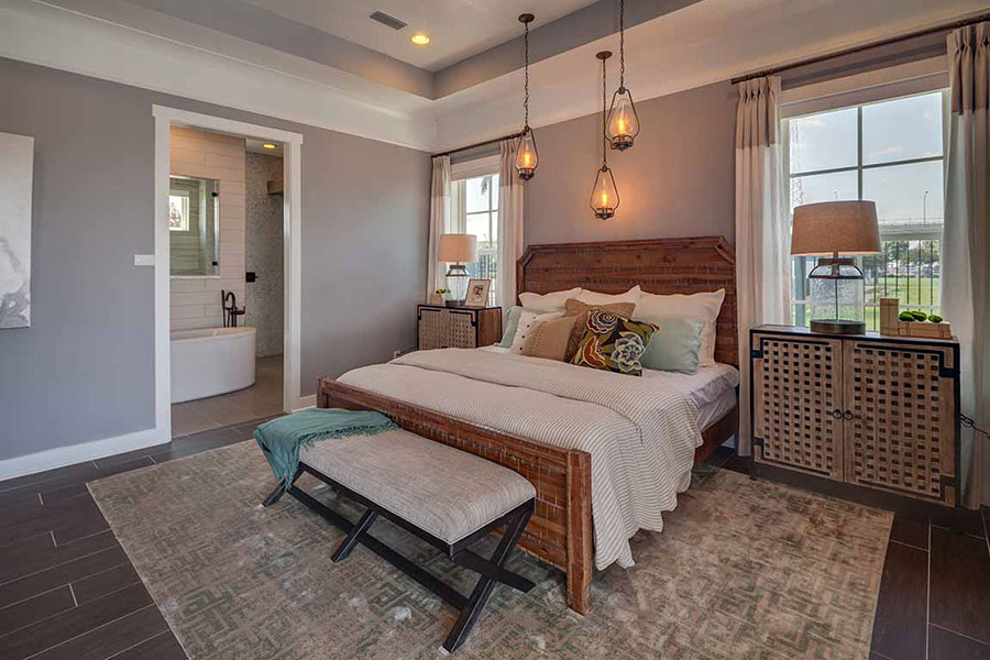 Bedroom decorated with a bed on a wood frame, lamps on large nightstands, a ceiling mounted pendant lights, and recessed lighting on dark brown luxury vinyl plank flooring.
