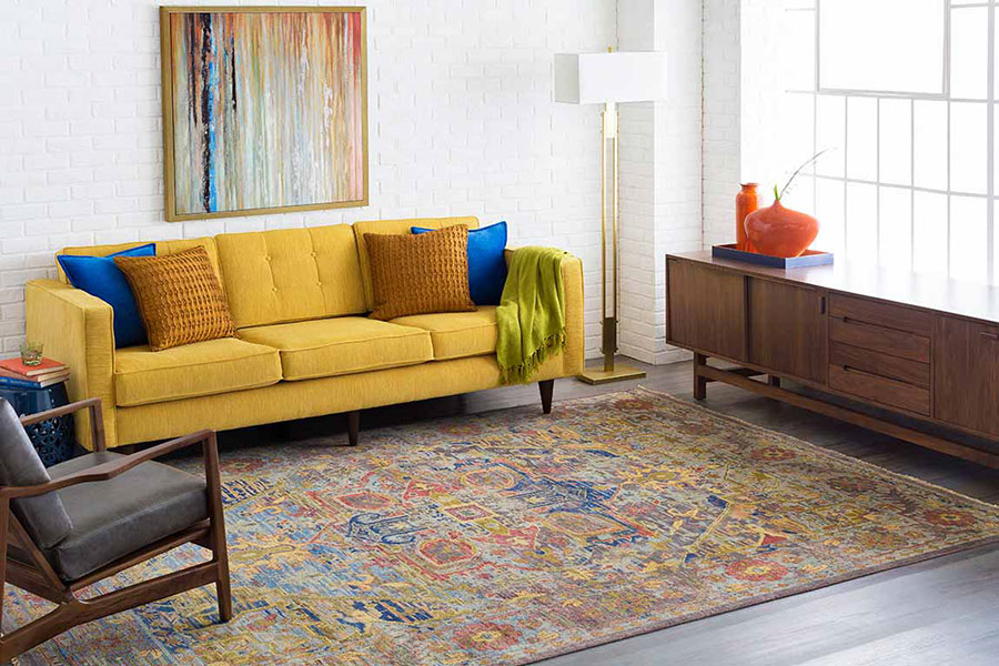 Living room with a yellow cloth couch, blue and gold throw pillows, grey chair on a large area rug and engineered floors.